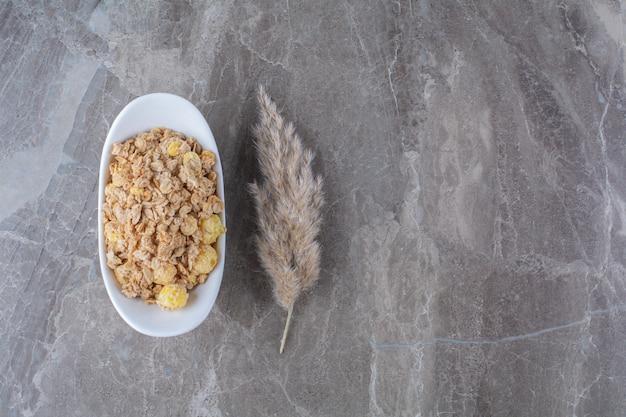 Белая тарелка, полная здоровых вкусных кукурузных хлопьев на сером фоне.