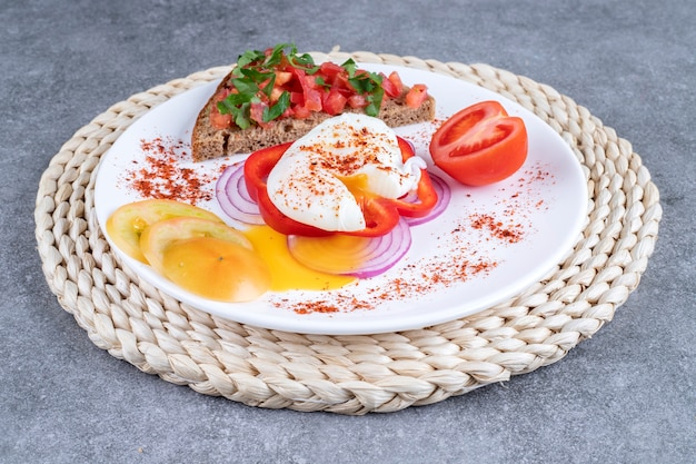 スライスした野菜とゆで卵がたっぷり入った白いお皿。高品質の写真