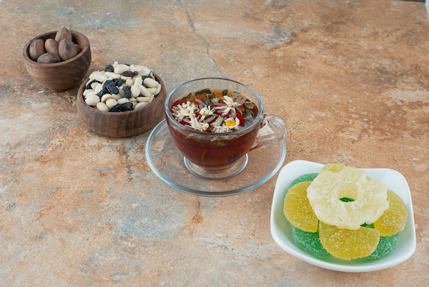 Белая тарелка, полная леденцов с сахарным желе и чашка травяного чая