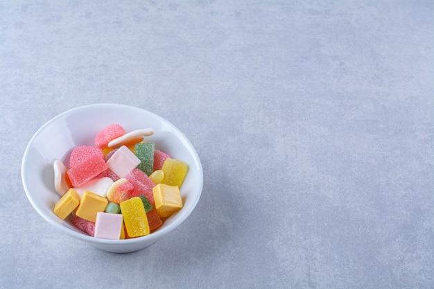 회색 표면에 달콤한 젤리 사탕으로 가득 찬 흰색 접시