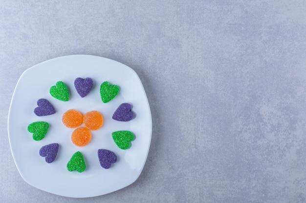 灰色のテーブルの上に甘いゼリーキャンディーでいっぱいの白いプレート。