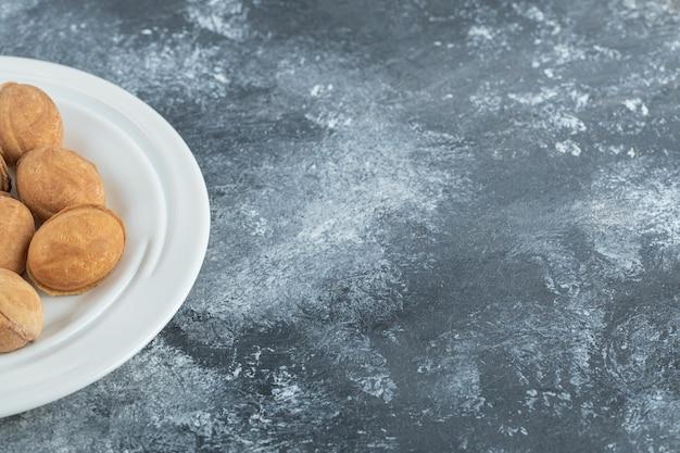 달콤한 호두 모양의 쿠키가 가득한 흰색 접시.
