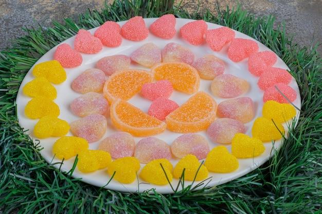 ジューシーでカラフルなゼリー菓子がいっぱい入った白いお皿。高品質の写真