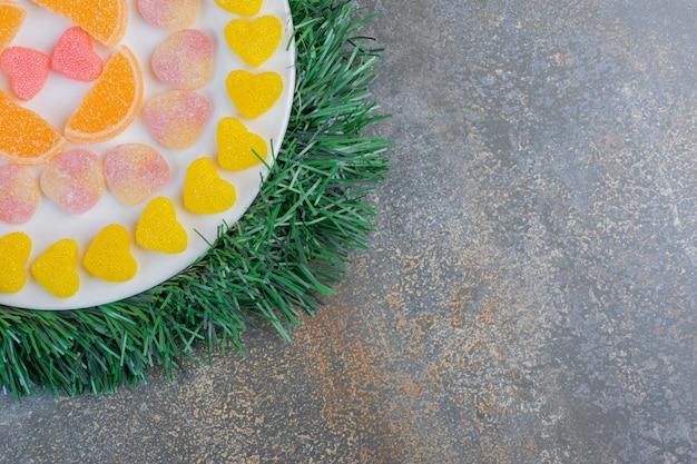 Белая тарелка с разнообразными сочными красочными желейными конфетами. фото высокого качества