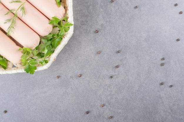 파슬리와 삶은 소시지의 흰색 접시.
