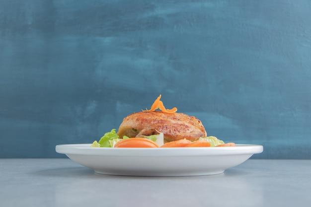 Белая тарелка куриного жареного мяса и нарезанной моркови.