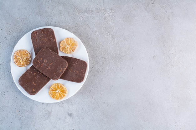 회색 배경에 얇게 썬 말린 레몬을 넣은 초콜릿 쿠키의 흰색 접시.