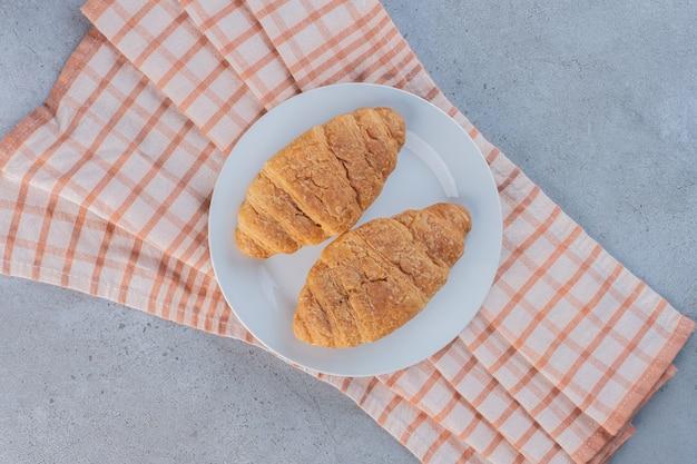 줄무늬 식탁보에 맛있는 달콤한 크루아상의 하얀 접시.