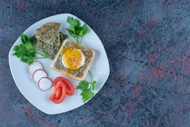 Белая тарелка вкусных тостов с мясом и овощами