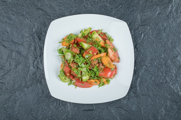 Белая тарелка вкусного овощного салата.