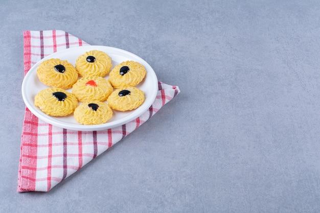 テーブルクロスにおいしい黄色いクッキーの白いプレート。
