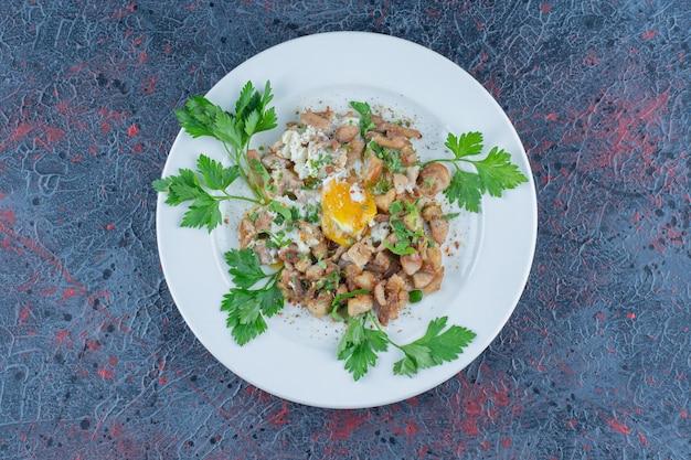 Белая тарелка жареного яйца с зеленью.