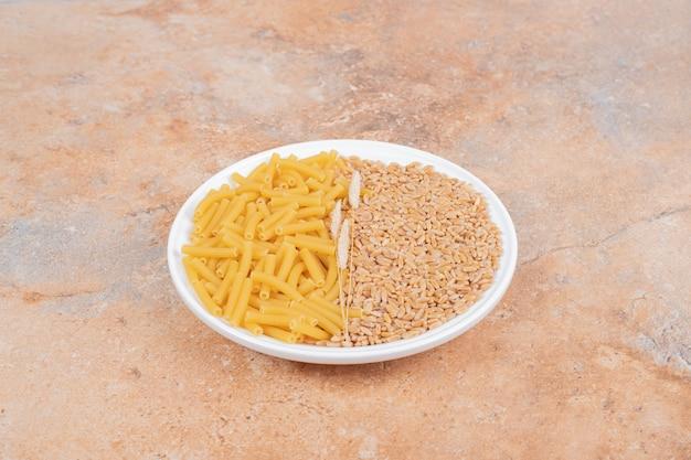 大理石の背景に生のマカロニと穀物と小麦の白いプレート。高品質の写真