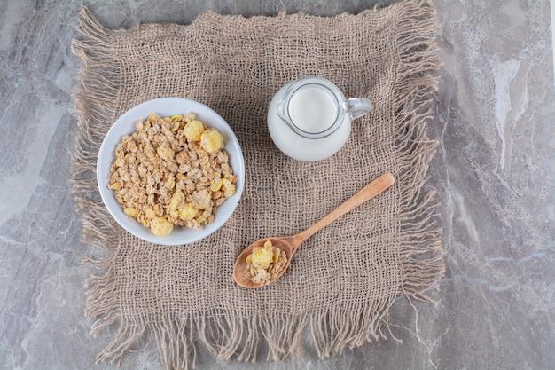 하얀 접시에 건강한 달콤한 콘플레이크가 있고 굵은 베옷에 우유 한 병이 있습니다.