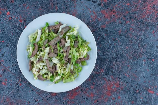 Белая тарелка мяса с овощным салатом.
