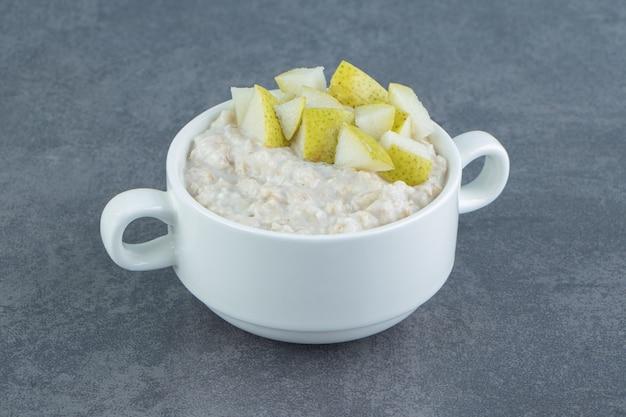 Белая тарелка овсяной каши с кусочками груши.