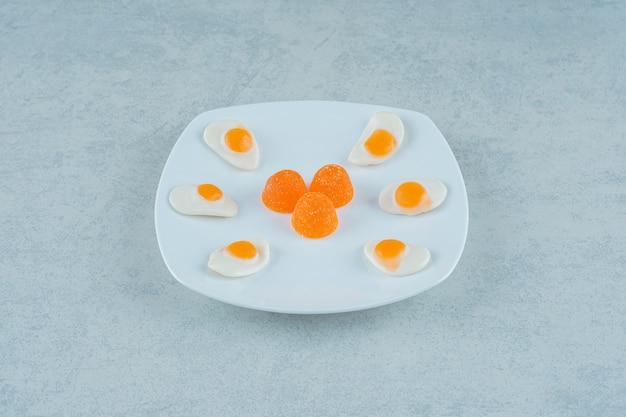 砂糖とゼリーのお菓子のスクランブルエッグとオレンジ色のゼリーキャンディーの白いプレート