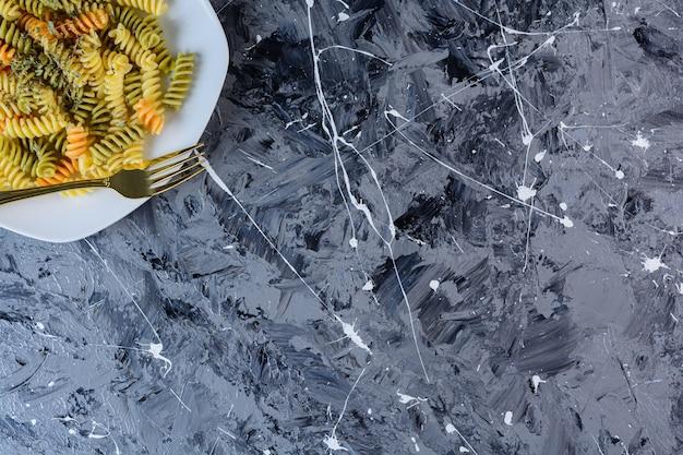 ケチャップとマヨネーズを添えた生のドライマルチカラーフジッリパスタの白いプレート
