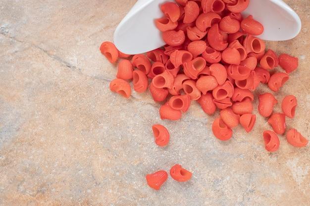 大理石のスペースに赤い未調理のマカロニの白いプレート。