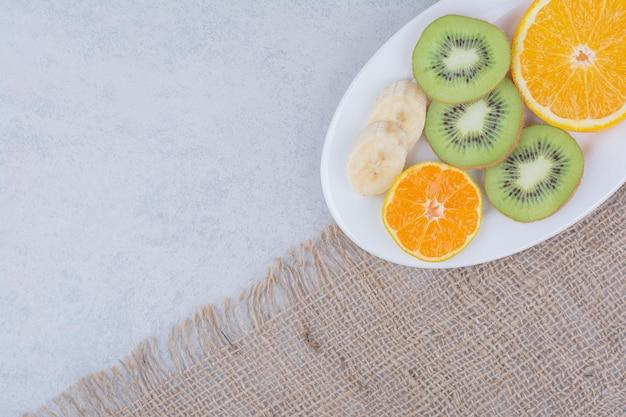 Белая тарелка нарезанных фруктов на вретище. фото высокого качества