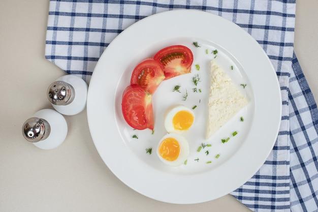 얇게 썬 토마토와 삶은 달걀의 흰 접시.