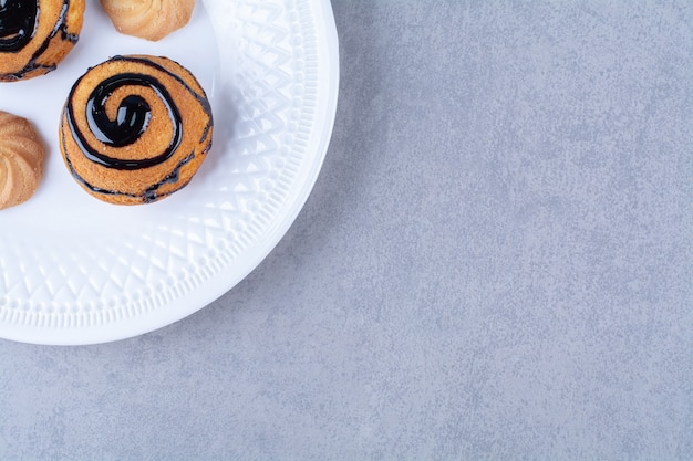 초콜릿 시럽을 곁들인 달콤한 맛있는 쿠키의 하얀 접시.