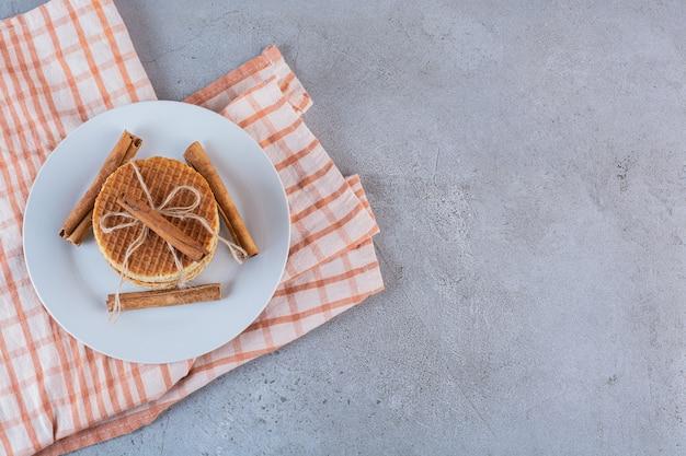 돌 표면에 계피 스틱 로프에 달콤한 와플의 흰색 접시