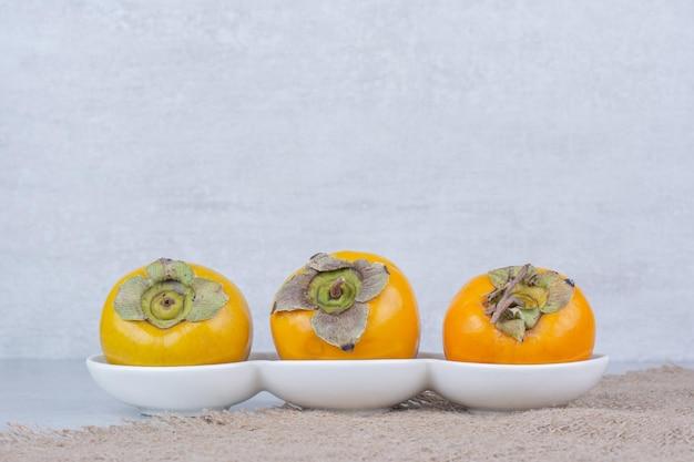 荒布の上に3つの甘い柿の白いプレート。高品質の写真