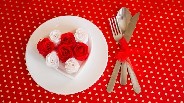 真っ赤な背景にナイフとフォークが付いた白いプレート。赤と白のバラの装飾。バレンタインデーのテーブルセッティング