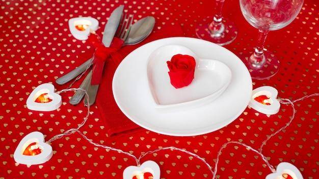Белая тарелка с ножом и вилкой на ярко-красном. белая тарелка в форме сердца. день святого валентина. вид сверху.