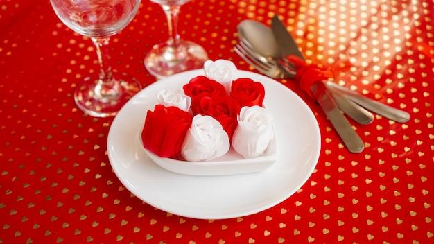 Белая тарелка с ножом и вилкой на ярко-красном. оформление красных и белых роз. сервировка стола на день святого валентина