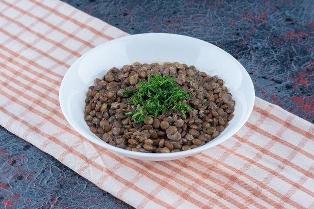テーブルクロスに豆とハーブの白いプレート
