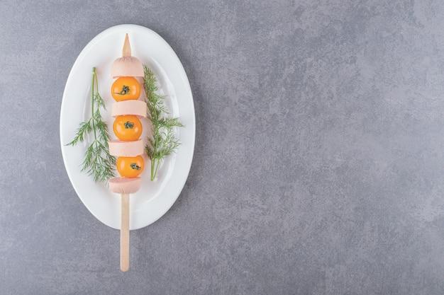 スライスしたソーセージとチェリーイエローのトマトを茹でた白いプレート。