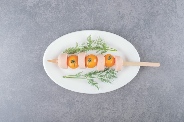 삶은 슬라이스 소시지와 체리 옐로우 토마토가 들어간 화이트 플레이트