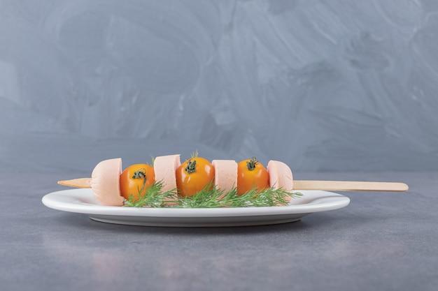 スライスしたソーセージとチェリーイエローのトマトを茹でた白いプレート