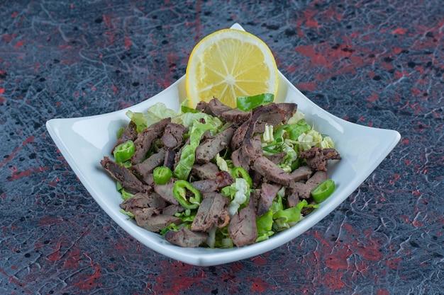 맛있는 고기와 허브를 곁들인 하얀 접시.