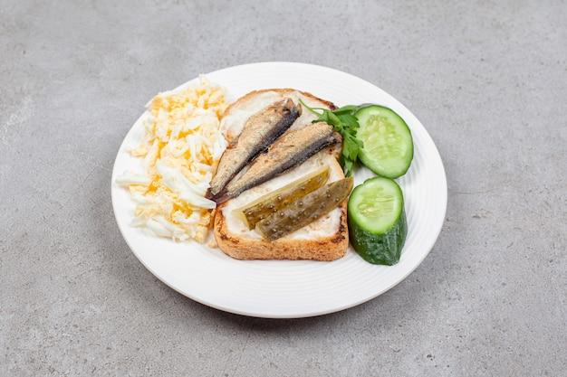 Белая тарелка с жареными тостами и шпротами