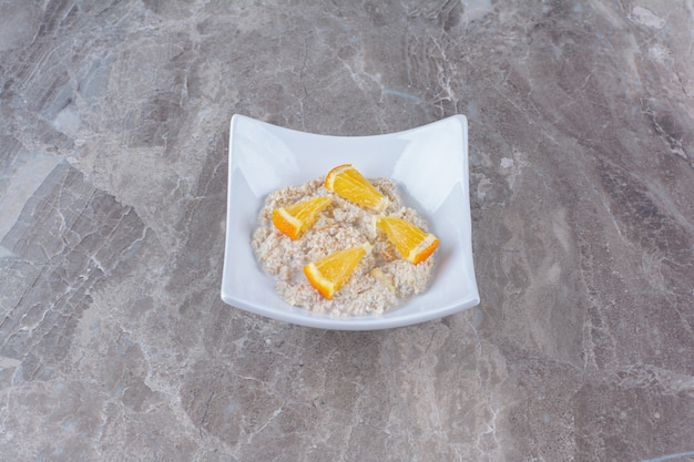 Белая тарелка со здоровой овсяной кашей и дольками апельсина.