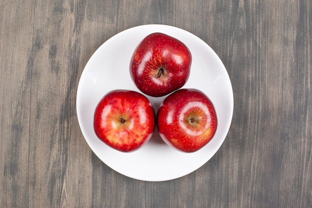木製のテーブルの上に赤いジューシーなリンゴと白いプレート。高品質の写真