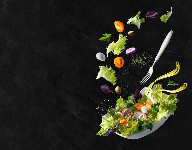 Белая тарелка с салатом и парящими в воздухе ингредиентами: маслинами, листьями салата, луком, помидорами, сыром моцарелла, петрушкой, базиликом и оливковым маслом. скопируйте пространство.
