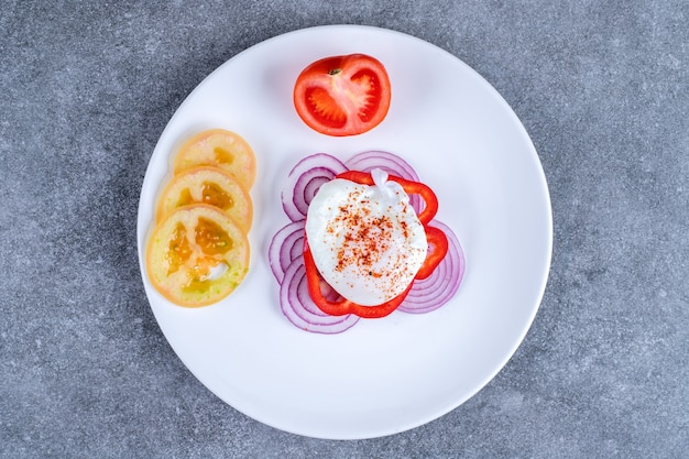 スライスしたトマトと玉ねぎの白いプレート。高品質の写真
