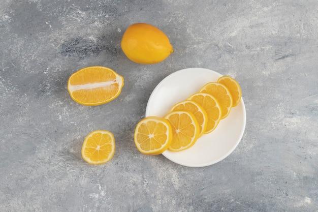 大理石の上に新鮮なレモンのスライスが付いた白いプレート。