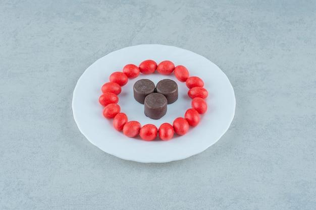 Белая тарелка со сладкими красными конфетами и шоколадным печеньем на белой поверхности