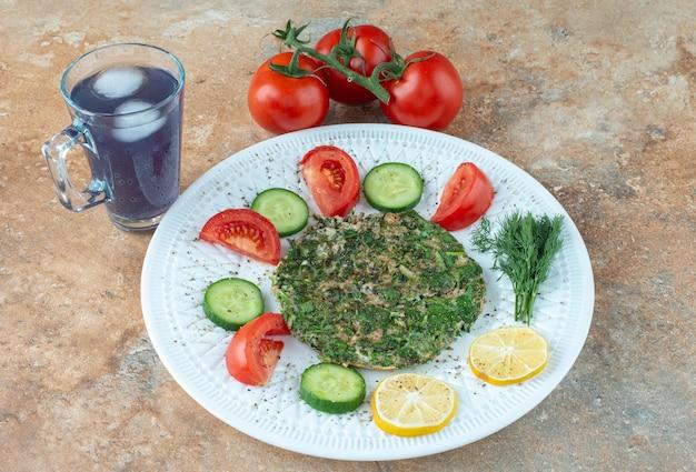Белая тарелка с овощами и стаканом сока.