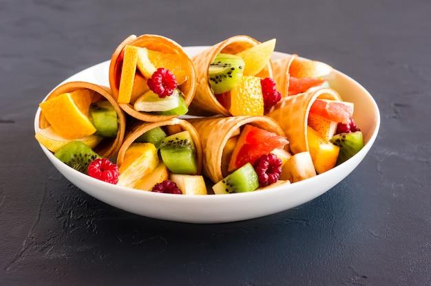Белая тарелка с вафельными рожками, наполненными фруктами на черном фоне.