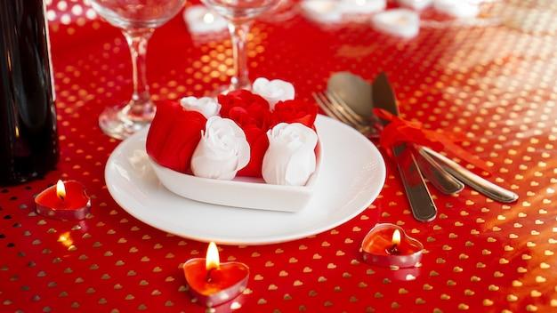真っ赤な背景にワイン、ナイフ、フォークが付いた白いプレート。赤と白のバラの装飾。バレンタインデーのテーブルセッティング