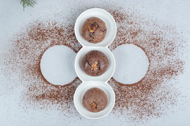 카카오 가루를 뿌린 초콜릿 쿠키가 든 하얀 접시