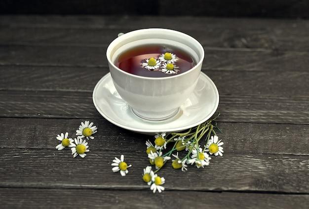 白磁の茶碗と受け皿にはカモミールティーが入っています。カモミールの花がいたるところにあります。