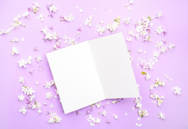 Белая открытка для текста и поздравлений лежит на светлом фоне среди цветов белой сирени. вид сверху