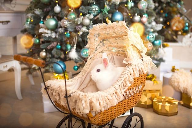 인형용 복고풍 유모차 안에 흰 토끼가 앉아 있습니다. 크리스마스 빈티지 장식, 조명 화환이 있는 크리스마스 트리. 새해. 집에서 애완 동물